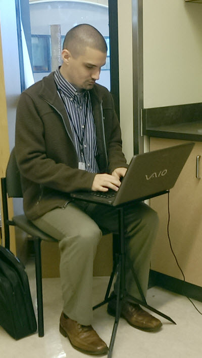 A trained transcriber, male, wearing a suit, working in the classroom