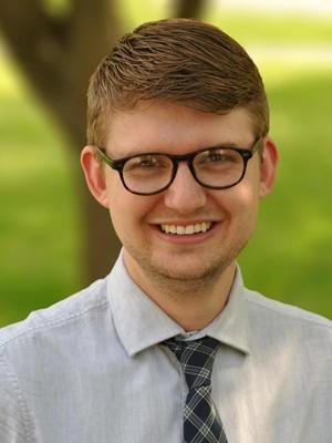 Chad Iwertz headshot wearing black glasses, white shirt, and a tie